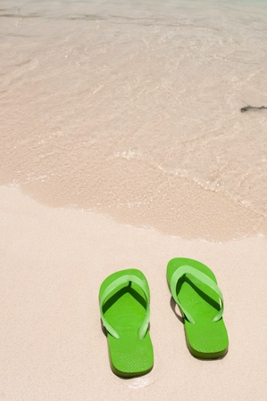 flops: green flip flops on the beach (copy-space available)
