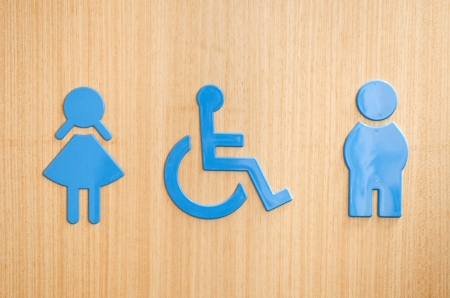 restroom sign: blue toilets WC sign for men, wheelchair and women (wooden background)