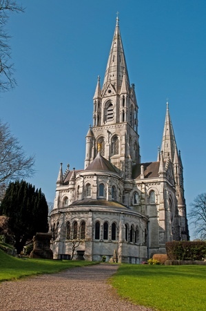 Saint Fin Barres cathedral in Cork, Ireland (garden view and blue sky background)