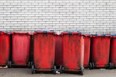 many red dirty garbage bins against a gray brick wall  copy-space available      photo