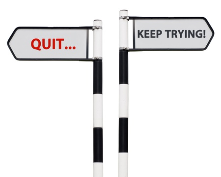 conceptual picture with keep trying and quit road signs isolated on white background Stock Photo