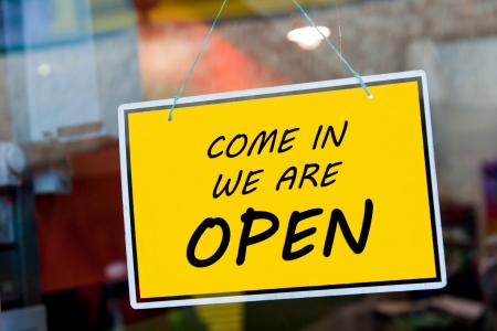 doors open: come in we are open sign hanging on a window door outside a restaurant, store, office or other Stock Photo
