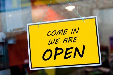 komen we open ondertekenen opknoping op een raam deur buiten een restaurant, winkel, kantoor of andere Stockfoto