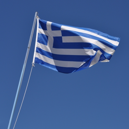 vibrant greek flag on a blue pole against a blue sky background photo