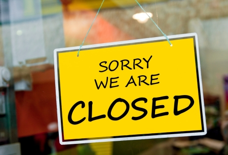 closed door: sorry we are closed sign hanging on a window door outside a restaurant, store, office or other