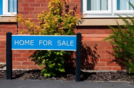 repossessing: home for sale real estate sign in front of new house with garden Stock Photo