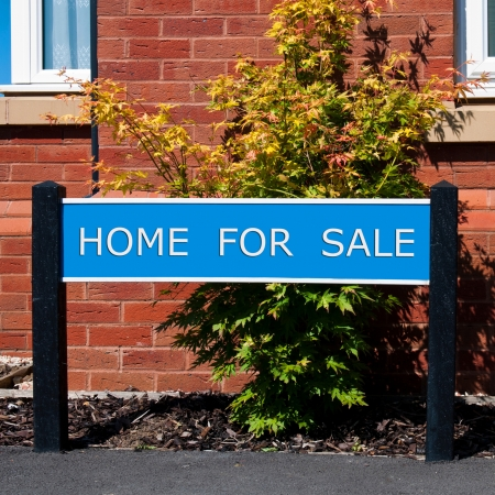 home for sale real estate sign in front of new house with garden photo