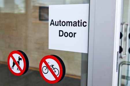 automatic door sign on shopping mall entrance  dogs and bicycles are forbidden  photo