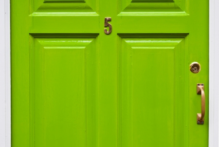 number lock: green typical residential house door in Ireland  number 5, golden lock and handle  Stock Photo
