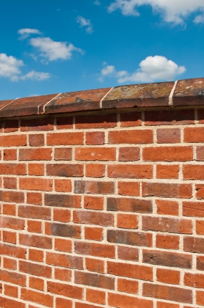 chipped: red brick wall against a gorgeous blue sky with clouds Stock Photo