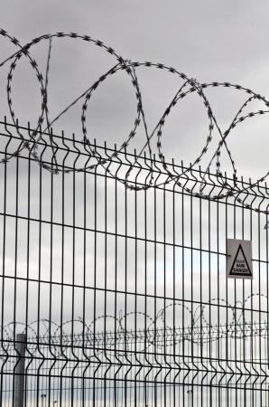 penitenciaria: alambre de púas y valla circular en un día muy nublado