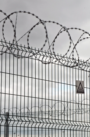 prison: circular barbed wire and fence on a very overcast day