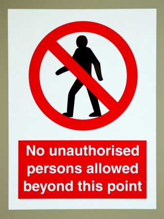 unauthorized: no unauthorised persons allowed beyond this  sign on a gray wall Stock Photo