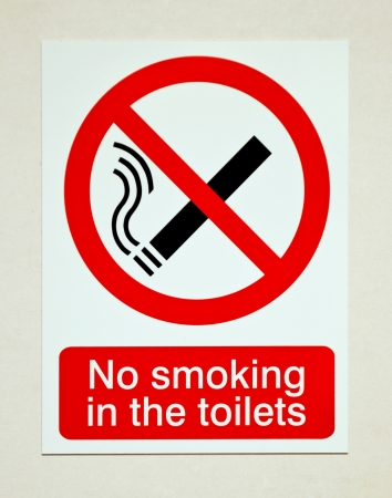 dont: no smoking in the toilets sign on white wall Stock Photo