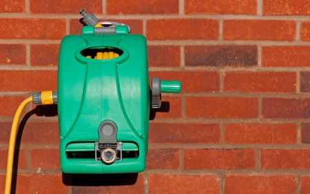 installed: garden hose reel kit installed on a brick wall  copy-space available