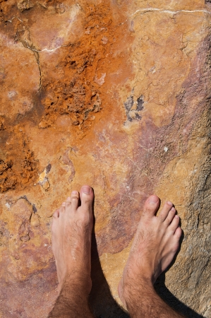 feet in sand: young man barefoot on rocky beach in Algarve, Portugal Stock Photo