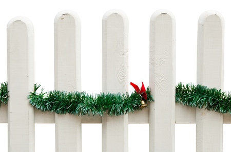 decorated Christmas fence with green tinsel and golden bell with bow (isolated on white background) photo