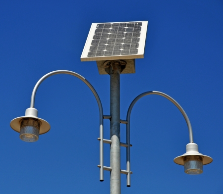 street lamp post with solar panel energy against blue sky photo