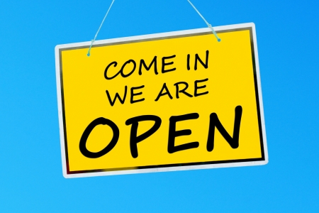 come in: come in we are open sign hanging against a vibrant blue sky Stock Photo
