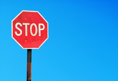 rusty stop sign on a metal pole against a vibrant blue sky (copyspace for your design) photo
