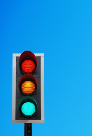 amber light: traffic lights against a vibrant blue sky (copy-space ready for your design)