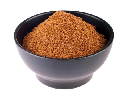 masala: garam masala powder on a black ceramic bowl  isolated on white background  Stock Photo