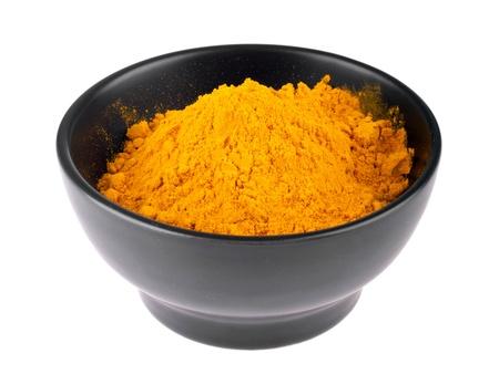 curry powder: curcuma powder on a black ceramic bowl  isolated on white background