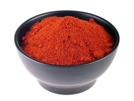 chili powder on a black ceramic bowl  isolated on white background  photo
