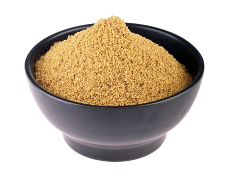 coriander powder on a black ceramic bowl isolated on white background