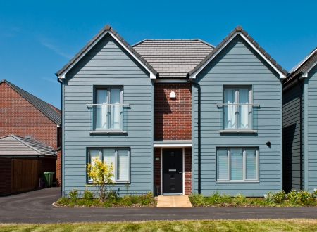 architecture detached house: detached british residential house (beach style) with small entrance garden (blue sky)
