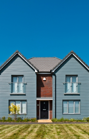 beach front: detached british residential house (beach style) with garden (blue sky) Stock Photo