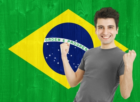 young sportsman fan cheering against the Brazilian flag photo