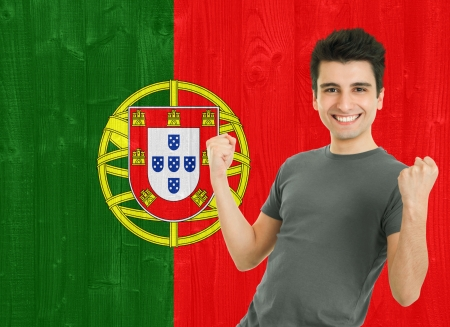 young sportsman fan cheering against the Portuguese flag photo