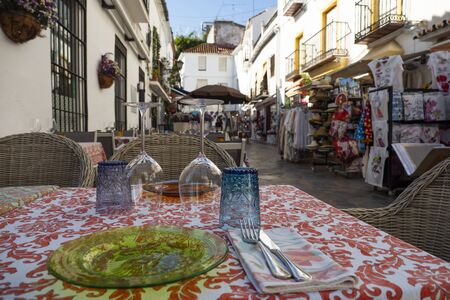 Table prepared for dinner on a tourist street. Historic district of Marbella, Malaga, Spain
