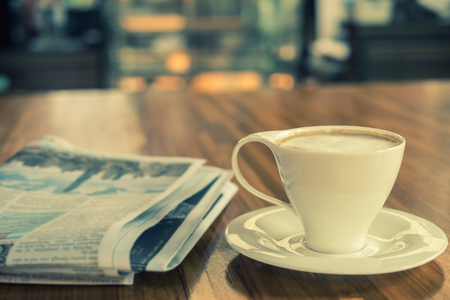 Cup of cappuccino with newspaper on the table in the morning , coffee shop background, warm tone