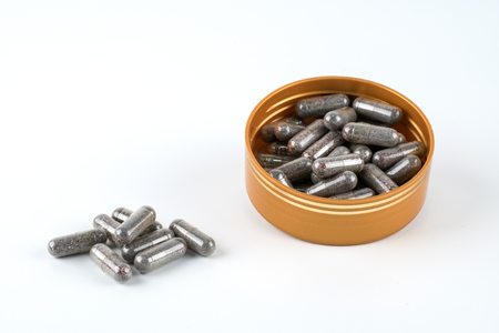 Herb pills medicine capsule with brown herbal leaf isolated on white background.