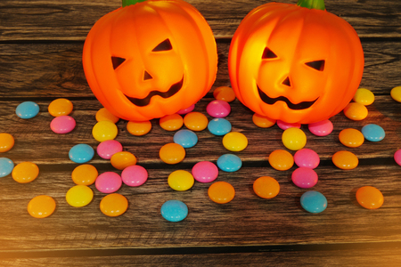 Halloween decoration trick or treat , jack-o-lantern pumpkin with candy snack on wooden background