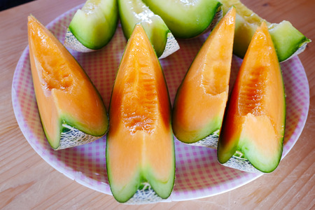 Close up fresh sliced melon with plate on wooden background at melon farm in Furano, Hokkaido, Japan. Juicy summer sweet fruit.