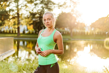 intentional: Woman with mobile phone getting ready for training in urban park (intentional sun glare) Stock Photo
