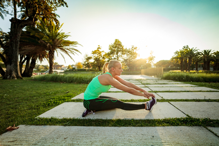 intentional: Woman training in urban park at sunset (intentional sun glare) Stock Photo