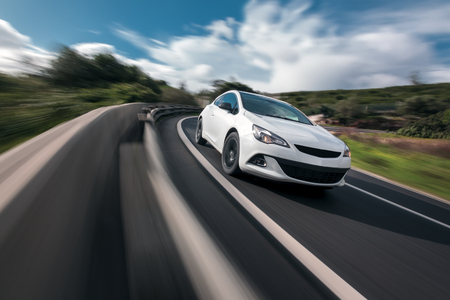 White car cornering in mountain road with speed blur Stockfoto