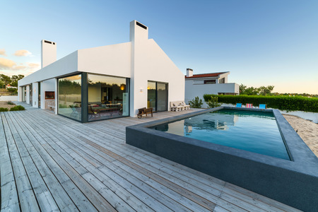 Modern house with garden swimming pool and wooden deck Archivio Fotografico - 104220891