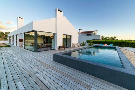 Modern huis met zwembad in de tuin en houten dek Stockfoto