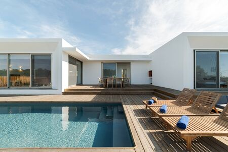 Wooden lounge chairs in modern villa pool and deck Stock Photo