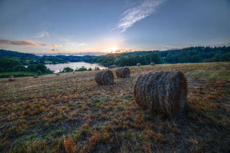 Sunset in a field with bales of grass beside the Minho River in the Camino de Santiago, in Portomarin, Lugo, Galicia