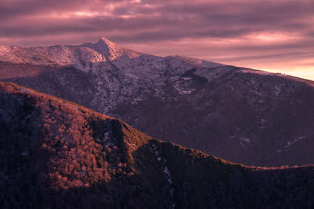 The lights of an overcast sunset dye purple the snowy mountains of Cervantes Ancares, Lugo, Galicia
