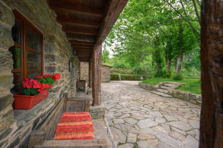 The Wooden Porch of a restored Old Manor House facing the cobblestone and the oak garden.
