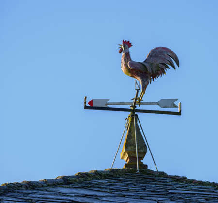 Rooster weathervane on the roof of a house