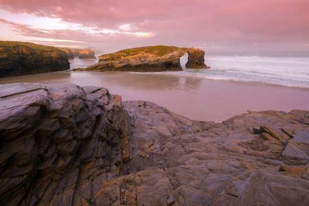 Sunrise with violet dyes on the famous As Catedrais beach
