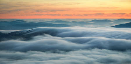 Wavy blankets of thick fog over valleys and hills at sunrise in Triacastela Galicia